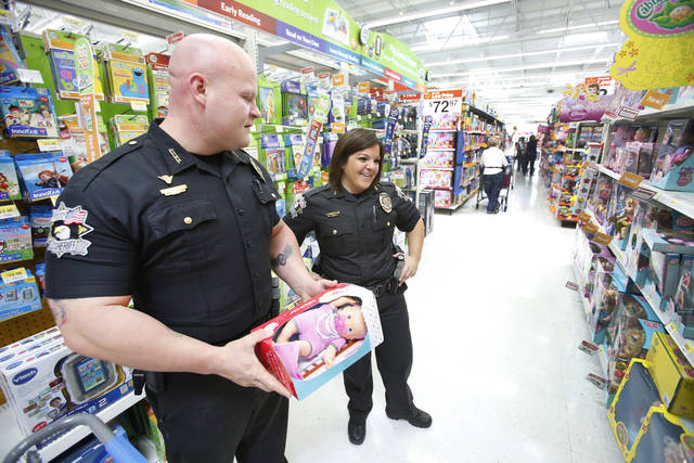 Oklahoma County sheriff�s deputies James Palmer and Jennifer Berryman shop for toys during a Sunbeam Family Services Christmas shopping event.