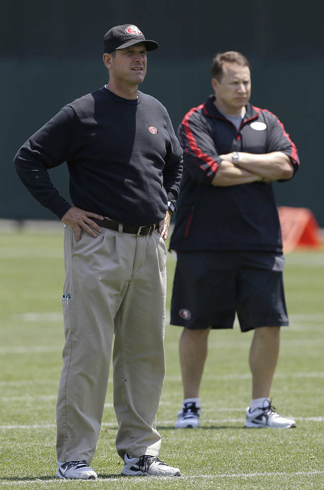 San Francisco 49ers coach Jim Harbaugh, left, and offensive consultant Eric Mangini watch the NFL football team's players practice in Santa Clara, Calif., Tuesday, June 4, 2013. (AP Photo/Jeff Chiu)