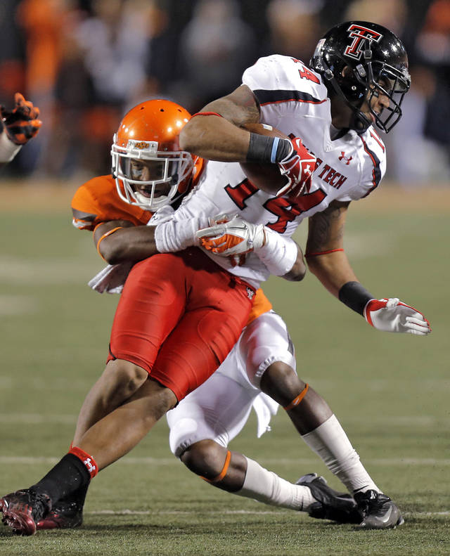 Oklahoma State's Kevin Peterson (1) stops Texas Tech's Darrin Moore (14) during the college football game between the Oklahoma State University Cowboys (OSU) and Texas Tech University Red Raiders (TTU) at Boone Pickens Stadium on Saturday, Nov. 17, 2012, in Stillwater, Okla.   Photo by Chris Landsberger, The Oklahoman