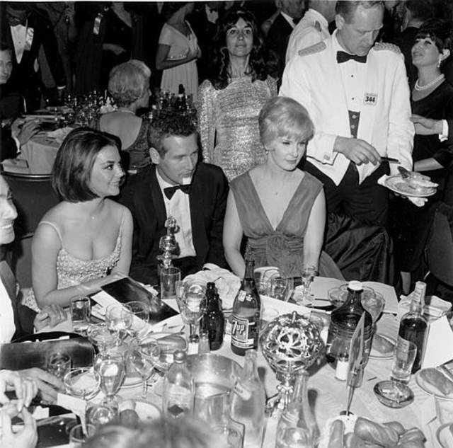 "Actor Paul Newman is flanked by actress Natalie Wood, left, and his actress-wife Joanne Woodward at the Hollywood Foreign Press Association Golden Globe awards reception in Hollywood, Ca., Jan. 31, 1966.  Wood, nominated for best actress in musical comedy for ""Inside Daisy Clover,"" received the World Film Favorite, female, award.  Newman received the World Film Favorite, male, award.  (AP Photo)"