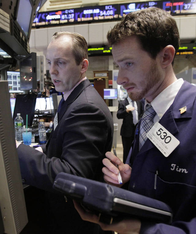 In this Dec. 15, 2011 photo, specialist Patrick Kenny, left, and trader Timothy Pastina work on the floor of the New York Stock Exchange. World stocks were buoyed Friday, Dec. 16, by improving U.S. economic indicators and the expected approval in Italy of an austerity plan intended to get the country's finances under control. (AP Photo/Richard Drew)