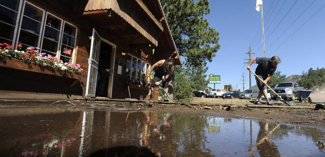 Vince Hanson, left, and Jody Logan of Eagle's Nest Wellness Center shovel mud from the entrance to the business along Highway 24 in Cascade, Colo. Tuesday, July 31, 2012. Highway 24 through the area was closed for several hours Monday as heavy rains caused flash floods below areas burned by the Waldo Canyon Fire. In Colorado alone, insurers estimate that wildfires have caused some $450 million in damage to personal property, and that number is expected to grow. (AP Photo/The Colorado Springs Gazette, Mark Reis)