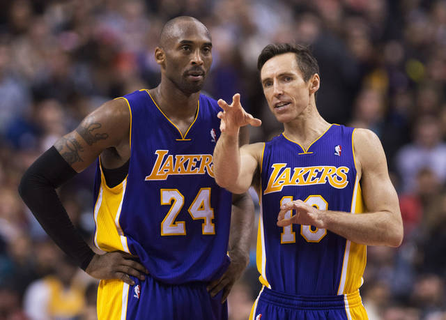 Los Angeles Lakers guards Kobe Bryant, right, and Steve Nash, right, talk during a time-out while playing against the Toronto Raptors during first half NBA basketball action in Toronto on Sunday Jan. 20, 2013. (AP Photo/THE CANADIAN PRESS,Nathan Denette) ORG XMIT: NSD109