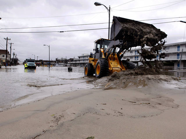 Crews work in flooded streets Tuesday, Oct. 30, 2012, in Ocean City, N.J., as they try to open drains and push the sand back toward the beach after the storm surge from Sandy flooded much of the town. Superstorm Sandy, the storm that made landfall Monday, caused multiple fatalities, halted mass transit and cut power to more than 6 million homes and businesses.  (AP Photo/Mel Evans) ORG XMIT: NJME116