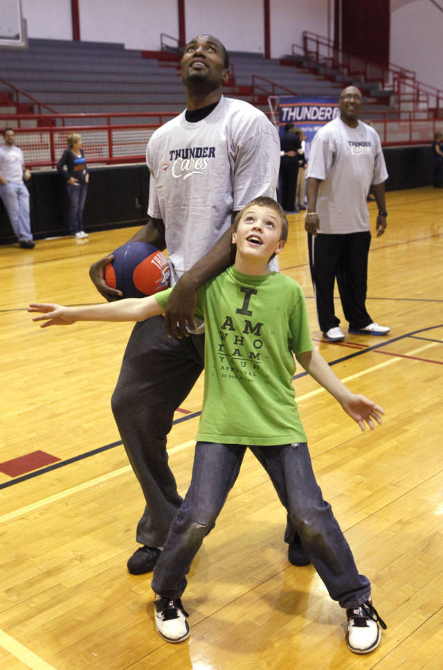 Sixth-grader Shaun Aberson tries to block Thunder player Serge Ibaka during a lesson at Cimarron Middle School in Edmond Thursday. PHOTO BY DAVID MCDANIEL, THE OKLAHOMAN <strong>David McDaniel - The Oklahoman</strong>