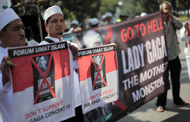 In this Friday, May 25, 2012 photo, Muslim hardliners of Islamic Defenders Front (FPI) hold banners during a protest against Lady Gaga in Jakarta, Indonesia. As the U.S. pop star canceled her sold out concert in Jakarta over security concerns after Muslim hardliners threatened to use violence against her, many started to question the extremists' double standard towards the raunchy dangdut shows performed almost every night by young Indonesian women who turn up everywhere from smokey bars and ritzy nightclubs to weddings and even circumcisions. Dangdut is the most popular music among lower class people in Indonesia. (AP Photo/Dita Alangkara)