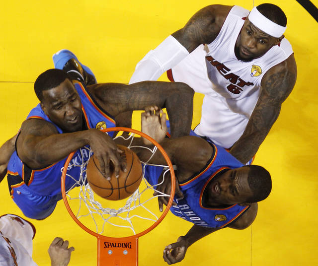 Oklahoma City Thunder center Kendrick Perkins (5) dunks as power forward Serge Ibaka (9) from Republic of Congo and Miami Heat small forward LeBron James (6) look on during the first half at Game 3 of the NBA Finals basketball series, Sunday, June 17, 2012, in Miami. (AP Photo/Mike Segar, Pool)  ORG XMIT: NBA142