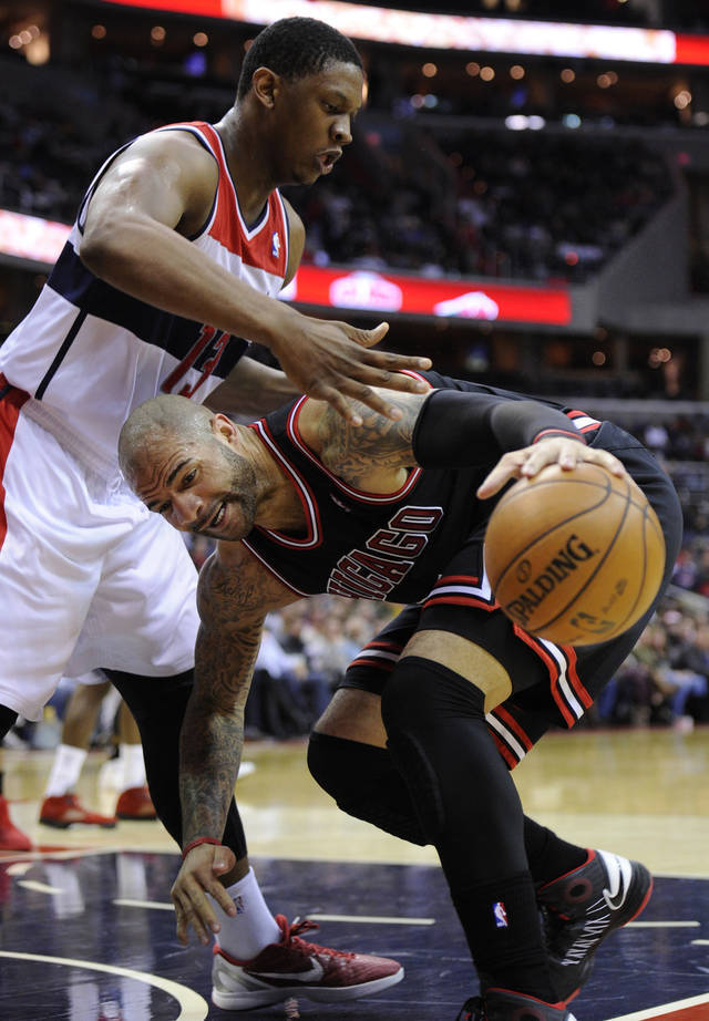Chicago Bulls forward Carlos Boozer, right, drives to the basket against Washington Wizards forward Kevin Seraphin (13) during the first half of an NBA basketball game, Saturday, Jan. 26, 2013, in Washington. (AP Photo/Nick Wass)