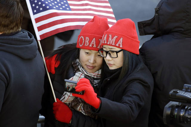 Khongorzul Battsengel, left, and Ariunbolor Davaatsogt both from Mongolia, take a picture of themselves as they wait for President Barack Obama in the 57th Presidential Inaugural Parade on Pennsylvania Avenue, Monday, Jan. 21, 2013 in Washington. Thousands marched during the 57th Presidential Inauguration parade after the ceremonial swearing-in of Obama. (AP Photo/Alex Brandon) ORG XMIT: DCAB106