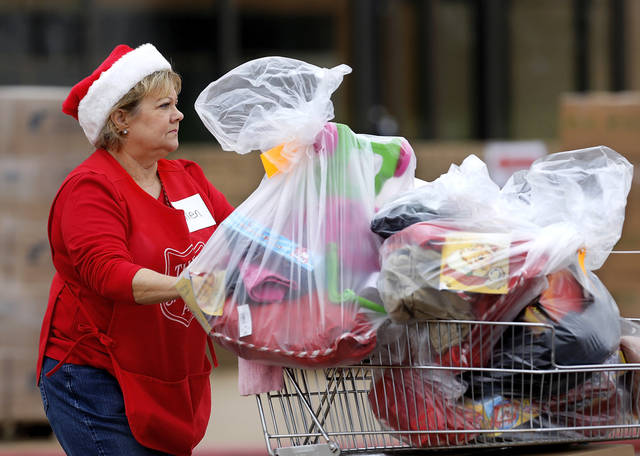 "Ellen McKenzie of Norman pushes a shopping cart loaded with gifts out of Crossroads Mall to a client's car. McKenzie said this is her 15th year to volunteer at the distribution event. She said working at the event ""makes me feel good."" She said she is ""very fortunate that I can do this"" to help others. She recruited another person to join her in volunteering this year. The Salvation Army and Feed the Children teamed to distribute bicycles and toys for children,  and handed out boxes of food for families at their annual distribution event Wednesday, Dec. 19, 2012. Salvation Army officials said 100 volunteers helped make the event go smoothly. The volunteers loaded bags of toys and bikes into vehicles of clients who had been pre-approved for assistance.  Many of the gifts were provided through the Salvation Army's Angel Tree program   Photo by Jim Beckel, The Oklahoman"