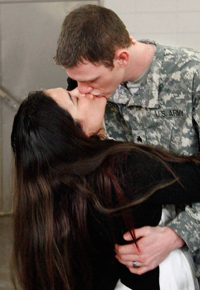 MIITARY DEPLOYMENT / ASHLEY BENNETT: Sgt. Micah Bennett, Tulsa, gets a kiss from his wife, Ashley,  after the 45th Infantry Brigade Combat Team Deployment Ceremony in downtown Oklahoma City, Wednesday, Feb. 16, 2011. This will be Bennett's second deployment.  Photo by Jim Beckel, The Oklahoman