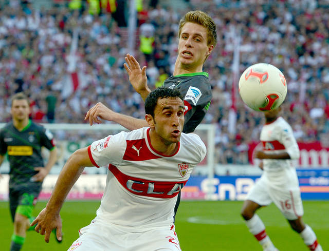 Stuutgart's  Cristian Molinaro, front, challenges for the ball with Moenchengladbach's Patrick Herrmann. top, during the German Bundesliga soccer match between VfB Stuttgart and Borussia Moenchengladbach  in Stuttgart, southern Germany Sunday, April 14, 2013.  (AP Photo/dpa, Bernd Weissbrod)