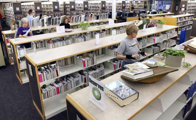 Library aides shelve reserved books as a part of the new self-serve reserve system at the Edmond branch of the Metropolitan Library System in Edmond, OK, Friday, Feb. 17, 2012. By Paul Hellstern, The Oklahoman