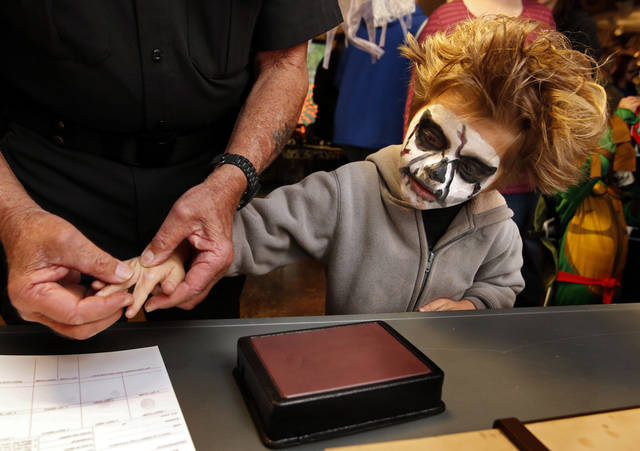 A Cleveland County sheriff�s deputy fingerprints Orion VunCannon, 6, at a Halloween event sponsored by the Discovery Cove Nature Center at Lake Thunderbird. PHOTOs BY STEVE SISNEY, THE OKLAHOMAN