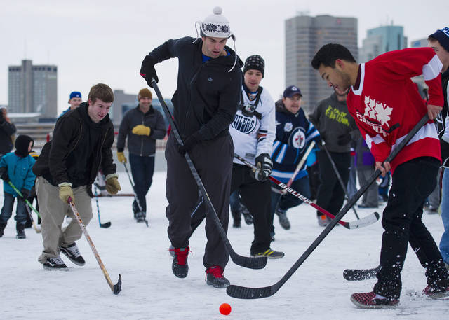   Winnipeg Jets captain Andrew Ladd, center, plays street hockey with hockey fans and a few fellow NHL players atop a parking garage at the Forks in Winnipeg, Manitoba, on Tuesday, Nov. 13, 2012. The lockout between the NHL and the players is in it&#039;s 59th day. (AP Photo/The Canadian Press, David Lipnowski)  