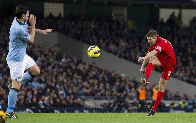 Liverpool's Steven Gerrard, right, scores past Manchester City's Gareth Barry during their English Premier League soccer match at The Etihad Stadium, Manchester, England, Sunday Feb. 3, 2013. (AP Photo/Jon Super)