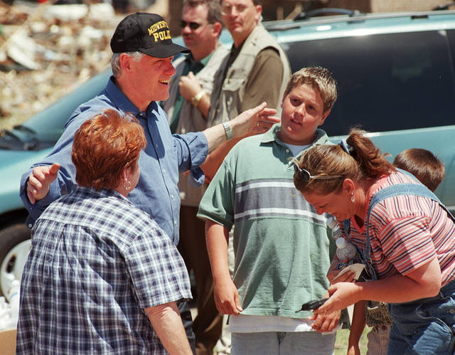 Tornado damage tour: President Bill Clinton in a Midwest City Police cap and with his arm on the shoulders of Sherrill Evett and her grandson Jeremy Walker laughs with Evett's daughter Tracy Walker as he leaves