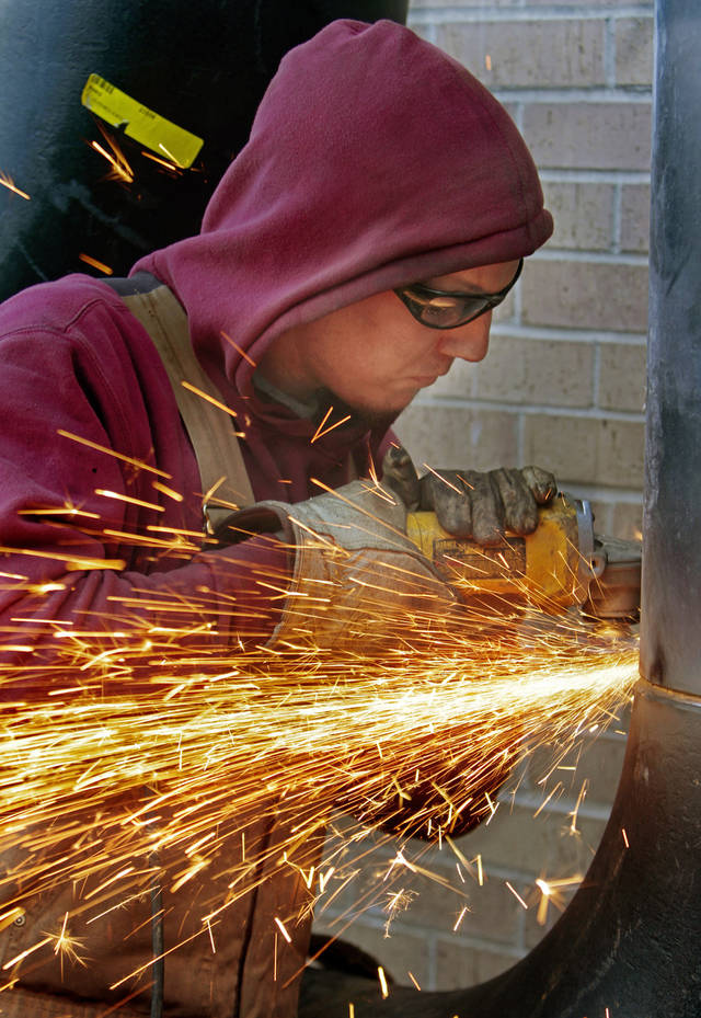 Welder Zack Robinson grinds pipe as workers install pipe for new air conditioning chillers at the Norman Public Library on Tuesday, Jan. 3, 2012, in Norman, Okla.  Photo by Steve Sisney, The Oklahoman