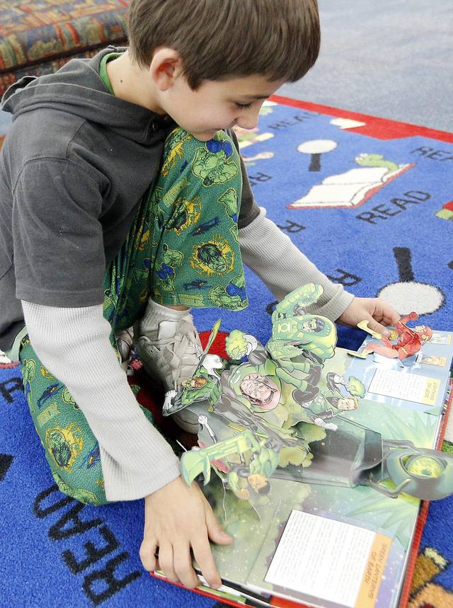 Right: Benjamin Stanley reads a book he received during a Winter Extravaganza at Orvis Risner Elementary in Edmond.
