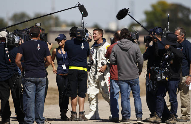 Felix Baumgartner, middle, of Austria, walks with his girlfriend Nici Oetl, facing at left, after Baumgartner successfully jumped from a space capsule lifted by a helium balloon at a height of just over 128,000 feet above the Earth's surface, Sunday, Oct. 14, 2012, in Roswell, N.M. (AP Photo/Ross D. Franklin) ORG XMIT: NMRF126