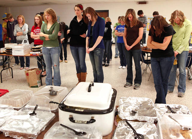 Students bow their heads as a prayer is offered before the food is served. Students, faculty and staff of Southern Nazarene University, prepared and served a traditional Thanksgiving meal as a service project Saturday afternoon, Nov. 20, 2010. David Bond, president of the university's Student Government Association, said his group partnered with the Alpha Lambda Delta sorority to plan and organize the holiday event. Bond estimated at least 100 college students and faculty participated in buying the food and preparing all the side dishes, pies and beverages for the guests. He said 15 turkeys were purchased and were professionally smoked by Red Dirt  B-B-Q  (cq) . Everyone in the community was invited to attend the meal.  Photo by Jim Beckel, The Oklahoman