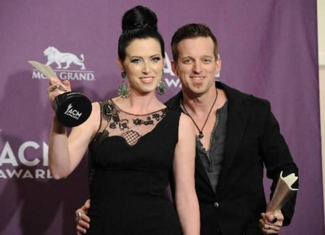 The couple shows off their ACM vocal duo of the year trophies.