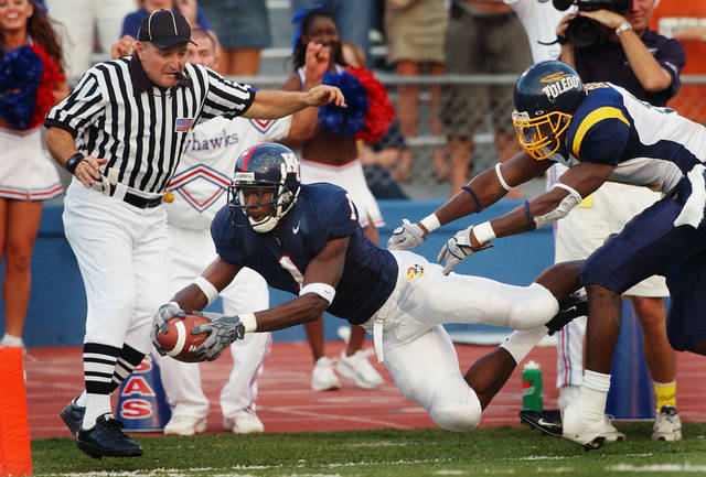 Kansas running back John Randle (1) dives for a touchdown past Toledo free safety Patrick Body (11) during the first quarter in Lawrence, Kan., Saturday, Sept. 11, 2004. Side judge Jeff Ulery, left, is in position for the call. Randle took an Adam Barmann pass 55 yards for the score. (AP Photo/Orlin Wagner) <strong>ORLIN WAGNER - ASSOCIATED PRESS</strong>