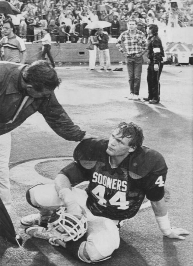 An OU fan consoles former Sooners linebacker Brian Bosworth after Texas rallied on a controversial fourth-quarter drive to tie Oklahoma 15-15 during the annual OU- Texas game at the Cotton Bowl in Dallas on Oct. 13, 1984. AP ARCHIVE PHOTO