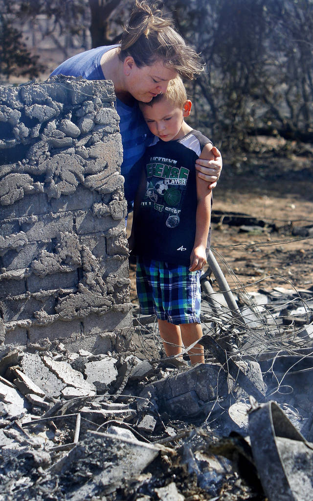 Tracy Streeper hugs five year-old grandson Jesse, as they stand on the north side of Streeper's destroyed home. The Streepers had lived in this house for one year. Residents  in Luther were allowed to return to the their homes early Saturday, Aug. 4, 2012, after they fled a rapidly moving wildfire yesterday that consumed at least seven structures on South Dogwood Street, leaving smoldering ashes where family homes once stood.  