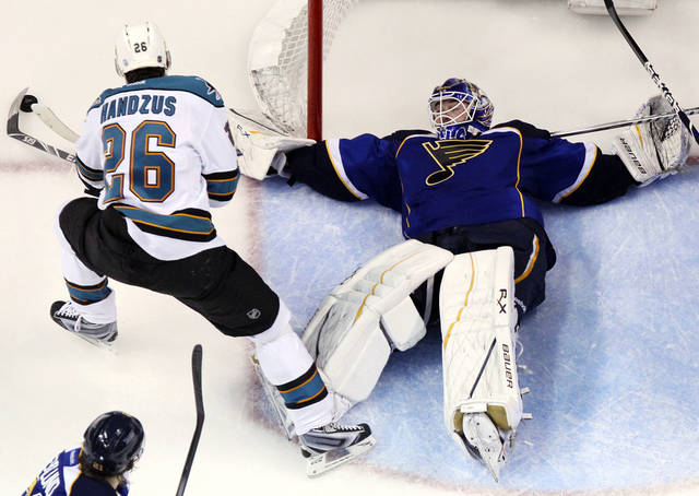 St. Louis Blues goaltender Brian Elliott defends against San Jose Sharks center Michael Handzus during the third period in Game 5 of an NHL Stanley Cup first-round hockey playoff series, Saturday, April 21, 2012, in St. Louis. The Blues won 3-1 and won the series 4-1. (AP Photo/St. Louis Post-Dispatch, Chris Lee) EDWARDSVILLE INTELLIGENCER OUT; THE ALTON TELEGRAPH OUT