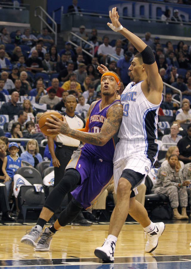 Phoenix Suns forward Michael Beasley (0) drives to the net under Orlando Magic forward Gustavo Ayon (19) of Mexico during the first half of an NBA basketball game in Orlando, Fla., on Sunday, Nov. 4, 2012. (AP Photo/Reinhold Matay)