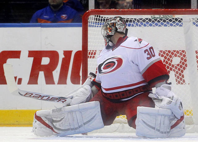 Carolina Hurricanes goalie Cam Ward (30) looks back as a shot by New York Islanders center Frans Nielsen (51) goes by him for a goal during the first period of an NHL hockey game at the Nassau Coliseum in Uniondale, N.Y., Monday, Feb.11, 2013. (AP Photo/Paul J. Bereswill)