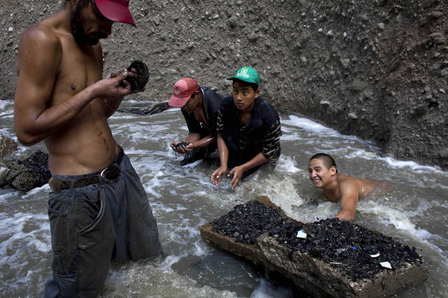 "In this photo taken Thursday Oct. 6, 2011, men search for scrap metal in contaminated water at the bottom of one of the biggest trash dumps in the city, known as ""The Mine,"" in Guatemala City. Hundreds of informal workers descend daily into the mounds of the landfill and the rushing waters that come from a storm tunnel and a sewer at the bottom of a gorge to search for scrap metal to sell. This activity known locally as ""mining"" is extremely dangerous due to mud slides and collapses, but earns many of them about 150 quetzals ($20 dollars) a day, nearly twice the minimum daily wage. AP Photo/Rodrigo Abd)"