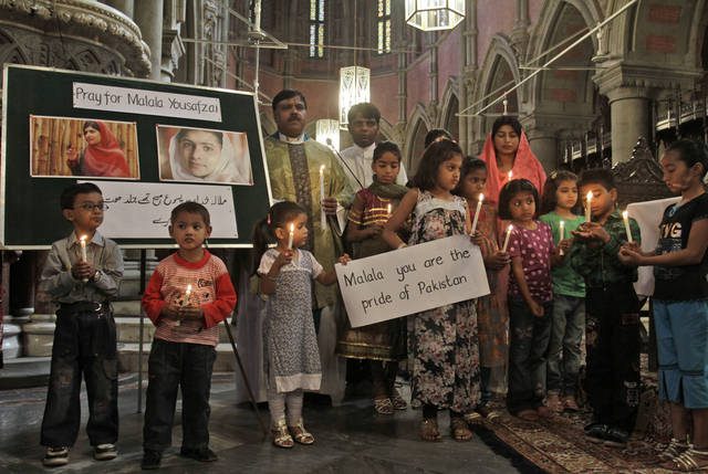 Pakistani children hold candles during a special prayer for the recovery of 14-year-old schoolgirl Malala Yousufzai, who was shot last Tuesday by a Taliban gunman for speaking out in support of education for women, at the Sacred Heart Cathedral Church in Lahore, Pakistan, Sunday, Oct. 14, 2012. The United Arab Emirates plans to send a specialized aircraft to serve as an ambulance for Yousufzai in case doctors decide to send her abroad for treatment, a Pakistani official said Sunday. (AP Photo/K.M. Chaudary)