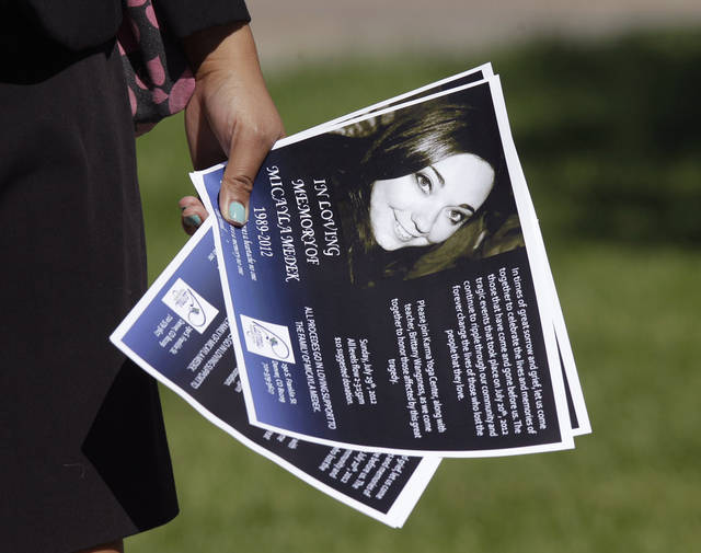 "A guest at the funeral of Aurora, Colo., movie theater shooting victim Micayla Medek, carries a notice with her photo on it, Thursday, July 26, 2012, prior to her funeral in Denver. Twelve people were killed and over 50 wounded in the shooting attack early Friday at a packed movie theater during a showing of the Batman movie, ""The Dark Knight Rises."" Police have identified the suspected shooter as James Holmes, 24. (AP Photo/Ted S. Warren)"
