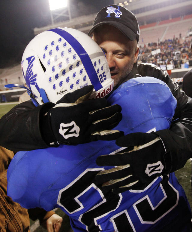 Hennessey coach Shannon Watford hugs running back Ivan Moreno after the Eagles won their second straight Class 2A state championship in December. Watford is leaving Hennessey to become Purcell's coach. PHOTO BY NATE BILLINGS, THE OKLAHOMAN