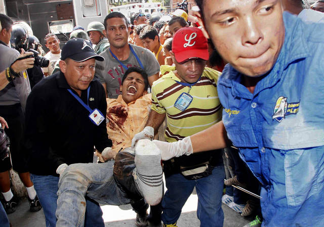 An injured prison inmate is carried into the hospital in Barquisimeto, Venezuela,  Friday, Jan. 25, 2013. A bloody riot erupted at the Uribana prison in the central Venezuelan city of Barquisimeto Friday when National Guard troops clashed with inmates. Venezuelan media reported that dozens were killed. It was the latest in a series of bloody riots in the country's prisons.(AP Photo/Alexander Sanchez/El Informador)