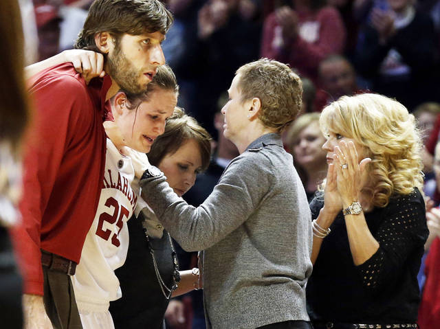 Whitney Hand, second from left, is helped off the court after an injury by strength coach Jozsef Szendrei, left, and trainer Carolyn Loon as she passes assistant coach Jan Ross, center, and head coach Sherri Coale during Thursday's game in Norman.  Photo by Steve Sisney, The Oklahoman