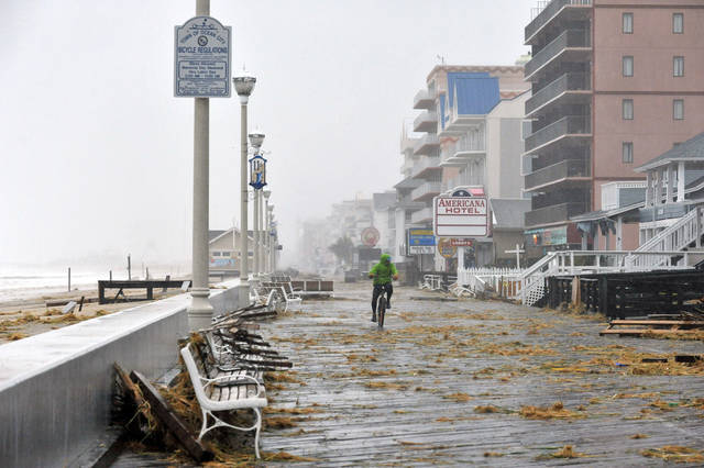 Ocean City resident Brandon Maynard bikes past benches strewn around the boardwalk Monday, Oct. 29, 2012, in Ocean City, Md. Sandy is combining with a wintry storm from the west and cold air from the Arctic. The superstorm could menace some 50 million people in the nation's most heavily populated corridor, from big East Coast cities to the Great Lakes. (AP Photo/The Daily Times, Laura Emmons)  NO SALES ORG XMIT: MDSAL102