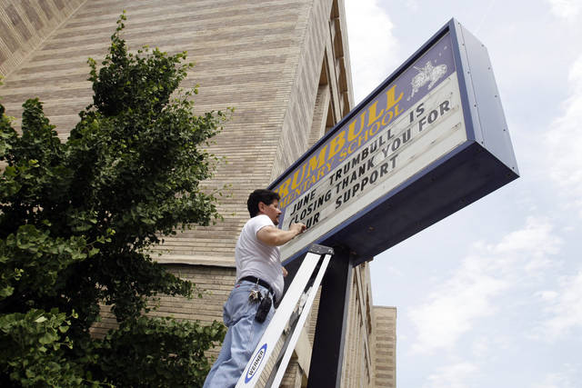"Custodian Felix Bonafe finishes placing letters on a sign announcing his school's closure on Monday, June 24, 2013, outside Trumbull Elementary School in Chicago. Trumbull, which served preschoolers through eighth-graders, is one of several public schools in Chicago that closed this month in an effort to save money and consolidate resources. Bonafe says he has received a temporary janitorial job at another school, though he's not sure how long it will last. His son, who would have been an eighth-grader at Trumbull, will move to another school in the fall. ""It's very sad. But what can you do?"" Bonafe says. ""What's done is done."" (AP Photo/Martha Irvine)"