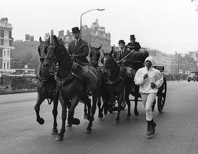 World heavyweight boxing champion Cassius Clay runs alongside a horse-drawn carriage, in Queen's Mews, Knightsbridge, London, May 11, 1966. Clay is in training for his fight against British challenger Henry Cooper on May 21. (AP Photo/Peter Kemp)