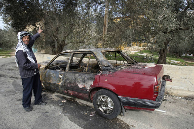 An elderly Palestinian man gestures as he stands next to a torched car Palestinians say was set on fire by Jewish extremists, in the West Bank village of Hares near Nablus, Wednesday, Dec. 14, 2011. Unknown arsonists torched an inactive Jerusalem mosque early Wednesday, provoking calls in Israel for a more effective crackdown on Jewish extremists suspected in a string of increasingly brazen acts of violence, that in recent months have expanded from the West Bank into Israel proper. Also Wednesday, cars in two West Bank villages were torched by Jewish extremists, Palestinian witnesses say. (AP Photo/Nasser Ishtayeh)