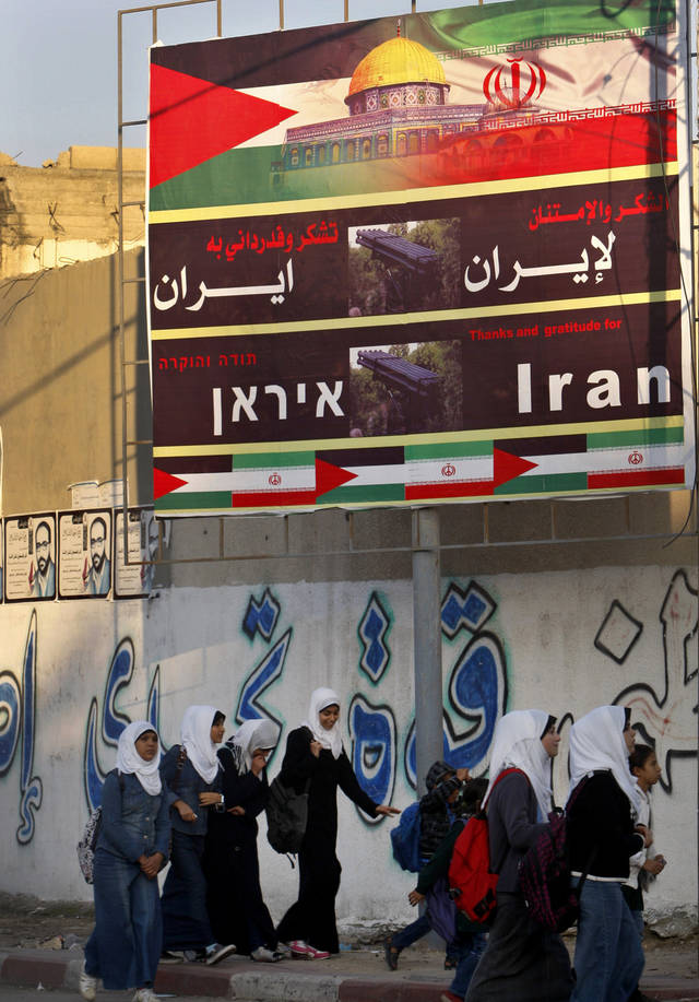 "Palestinian school girls pass a billboard covered by national and Iranian flags with Arabic reads ""thanks and gratitude to Iran"", in Gaza City, Wednesday, Nov. 28, 2012. Residents of the Gaza Strip have plastered large billboards in key locations thanking Iran for its help during a recent eight-day battle against Israel. The posters reflect the strong ties between Iran and the Hamas and Islamic Jihad militant groups in Gaza. Israel considers Iran to be its most dangerous enemy, citing Iran's support for the militants and its suspect nuclear program. During the fighting, Gaza militants groups fired hundreds of rockets into Israel, including Iranian-made missiles reaching as far as Tel Aviv. (AP Photo/Adel Hana)"