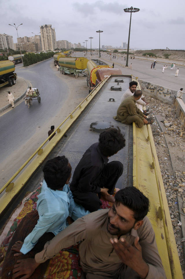 Pakistani men sit on top of oil tankers, which were used to transport NATO fuel supplies to Afghanistan, and watch a cricket match, seen at right, in Karachi, Pakistan, Wednesday, May 16, 2012. NATO has invited Pakistan's president to the upcoming Chicago summit on Afghanistan, the strongest sign yet that Islamabad is ready to reopen its western border to U.S. and NATO military supplies heading to the war in the neighboring country. (AP Photo/Shakil Adil)