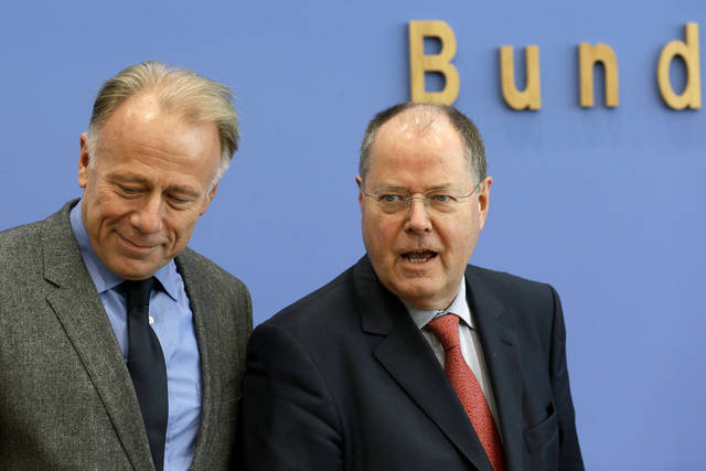 Opposition  top candidates for the 2013 federal elections, German Social Democratic Party top candidate , Peer Steinbrueck, right, and the Green Party top candidate, Juergen Trittin, left, pose for the media prior to a press conference in Berlin, Germany, Wednesday, Dec. 12, 2012. (AP Photo/Michael Sohn)