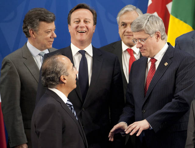 United Kingdom Prime Minister David Cameron laughs as Canadian Prime Minister Stephen Harper speaks with Mexican President Felipe Calderon as they wait for the start of the family photo at the G-20 Summit in Los Cabos, Mexico, Monday June 18, 2012. (AP Photo/The Canadian Press, Adrian Wyld)