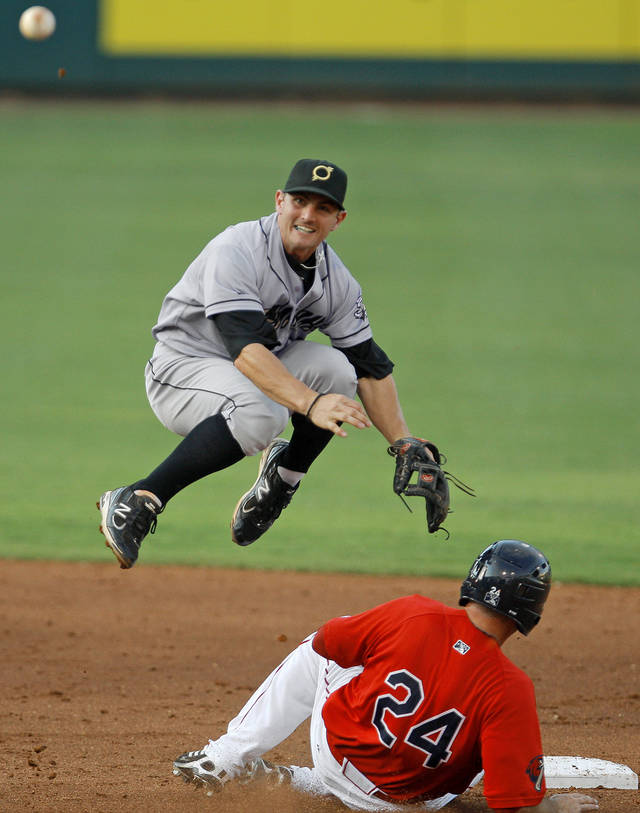 Johnny Giavotella of the Omaha Storm Chasers leaps over Drew Locke of the Oklahoma City RedHawks to make the throw for a double play in the second inning of the baseball game at RedHawks Field at Bricktown in Oklahoma City, Friday, July 8, 2011. Photo by Bryan Terry, The Oklahoman ORG XMIT: KOD