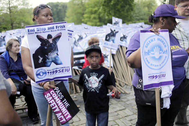 "Justin Williams, 6, center, waits with his grandmother Denise Robinson, left, before the start of a silent march to end the ""stop-and-frisk"" program in New York, Sunday, June 17, 2012. Thousands of protesters from civil rights groups walked down New York City's Fifth Avenue in total silence on Sunday as they marched in defiance of ""stop-and-frisk"" tactics employed by city police. (AP Photo/Seth Wenig)"
