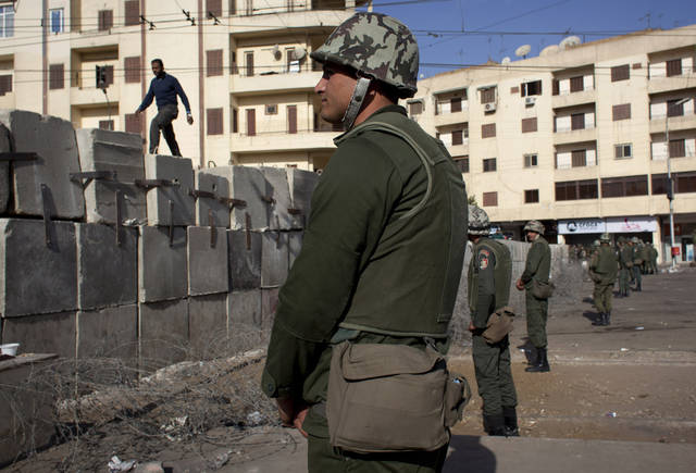 Egyptian army soldiers stand guard in front of the presidential palace, in Cairo, Egypt, Sunday, Dec. 9, 2012. Egypt's liberal opposition has called for more protests on Sunday after the president made concessions overnight that fell short of their demands to rescind a draft constitution going to a referendum on Dec. 15. (AP Photo/Nasser Nasser)