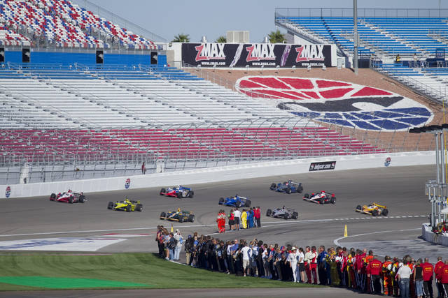 IndyCar fans and team members watch as drivers take five tribute laps in honor of Dan Wheldon, a two-time Indianapolis 500 winner died following a crash in the IndyCar Series' Las Vegas Indy 300 auto race earlier Sunday, Oct. 16, 2011 in Las Vegas. (AP Photo/Eric Jamison)